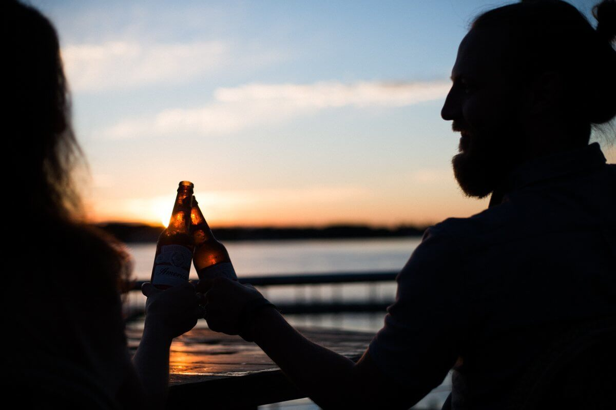 silhouette of man and woman holding beer
